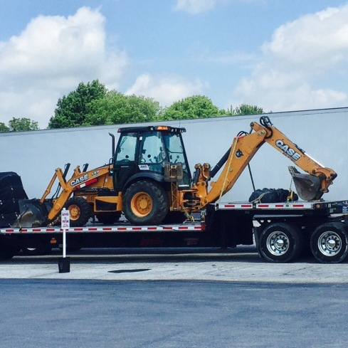 Picture of a Case 580 Combination Backhoe sitting on a step-deck trailer.